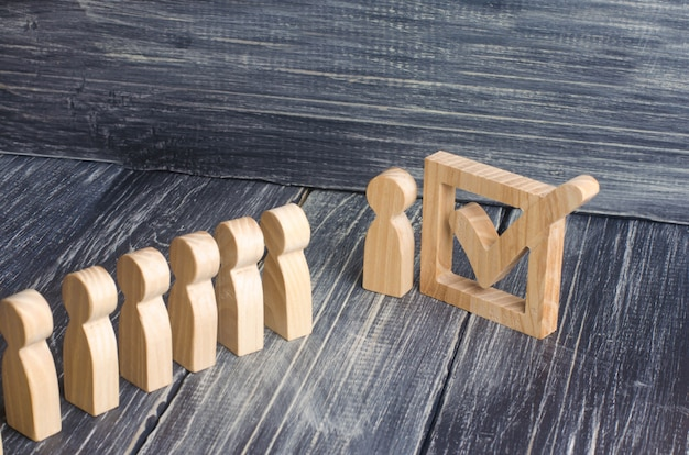 Три деревянные человеческие фигуры стоят рядом с галочкой в коробке Premium Фотографии