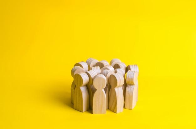 Группа деревянных фигурки людей на желтом фоне. толпа, встречи, общественная деятельность. Premium Фотографии