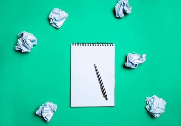 紙ボールの中で緑の背景にペンが付いている白いノート。生成の概念 Premium写真