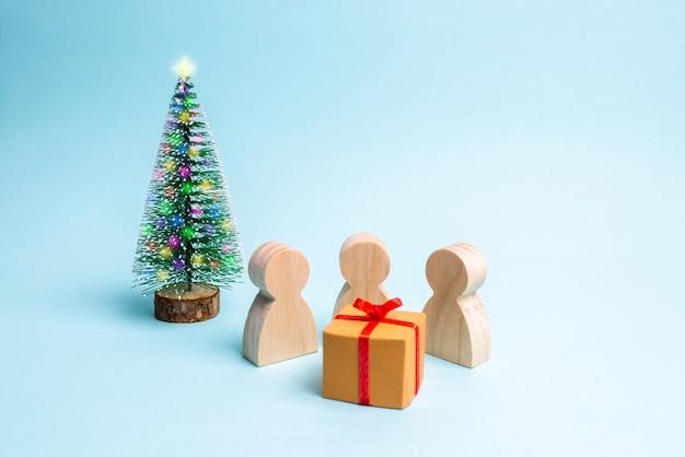 人々はその贈り物の周りに集まり、それを開く準備ができています。 Premium写真