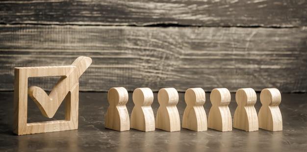 木製の人物は箱の中の目盛りの隣に立っています。選挙の概念 Premium写真