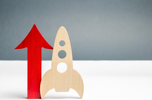 木製のロケットと上向きの矢印。スタートアップの概念スタートアップのための資金を集めるというコンセプト。 Premium写真