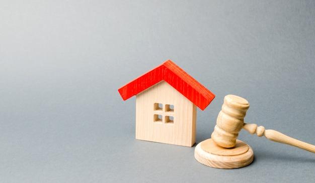 ミニチュア木造住宅と裁判官のハンマー。 Premium写真