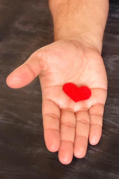 男は彼の手に赤いハートを握る Premium写真