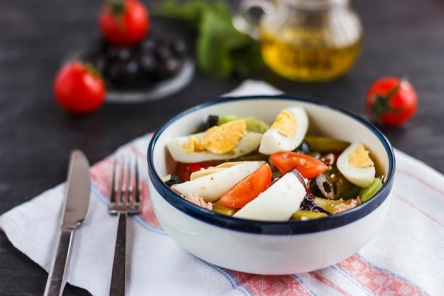 Салат нисуаз с тунцом, зеленой фасолью, базиликом и свежими овощами Premium Фотографии