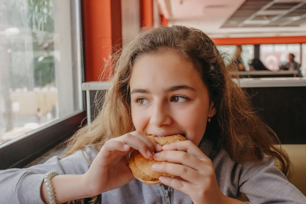 カフェでハンバーガーを食べて食欲を持つかなり若い十代の少女 Premium写真