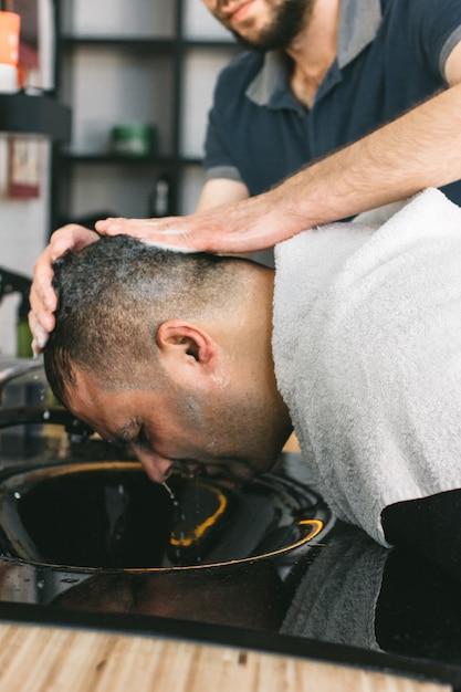 美容師は、理髪店で髪を切った後、男性の頭を洗います。 Premium写真