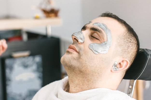 男性の顔のワックス。理容師は、トルコ人男性の顔からシュガーをして髪を取り除きます。 Premium写真