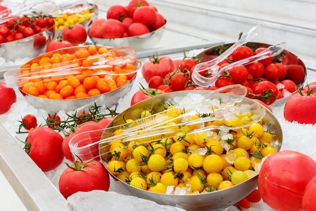 氷のボウルに黄色とピンクのトマト Premium写真