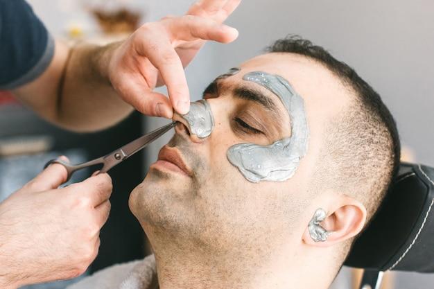 男の鼻の毛を切る。男性の顔のワックス。理容師は、トルコ人男性の顔からシュガーをして髪を取り除きます。 Premium写真