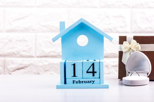 День святого валентина на кубиках календаря с подарочной коробкой и бриллиантовым кольцом Premium Фотографии