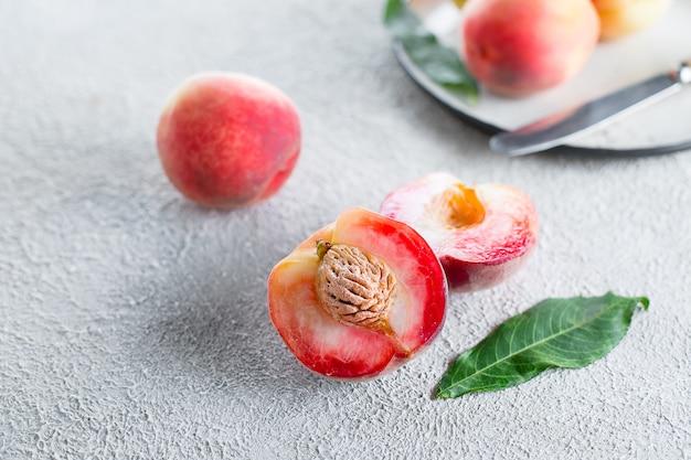 Свежие персики. персики на легком бетоне Premium Фотографии
