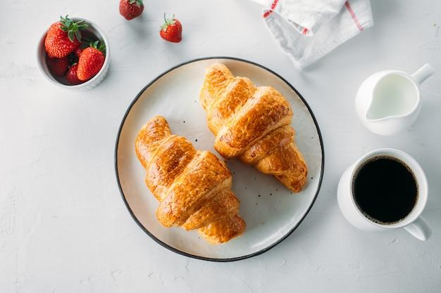 一杯のコーヒー、焼きたてのクロワッサン、木製の背景に新鮮なイチゴ Premium写真