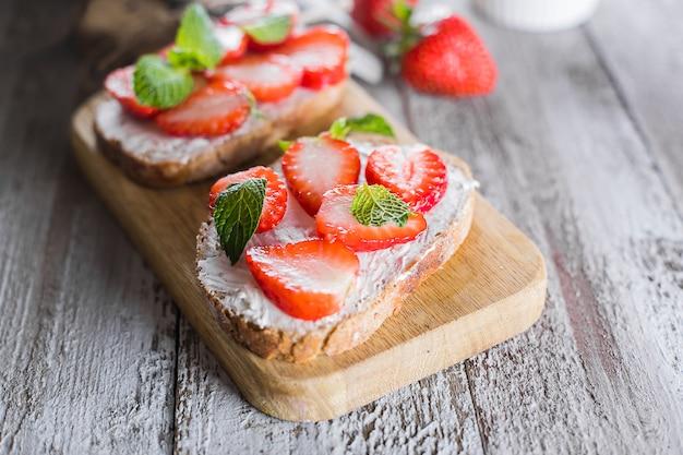 Два тоста или брускетта с клубникой и мятой на твороге на деревянной доске на столе Premium Фотографии