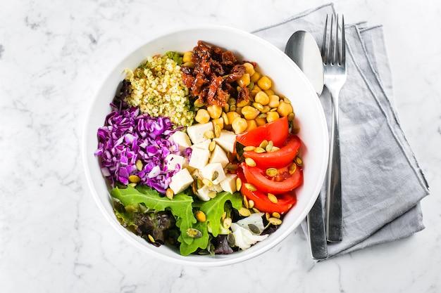 ベジタリアン、健康、デトックス食品のコンセプト。ベジタリアン仏丼。生野菜、豆腐、カトラリーと白いボウルのブルガー。上面図 Premium写真