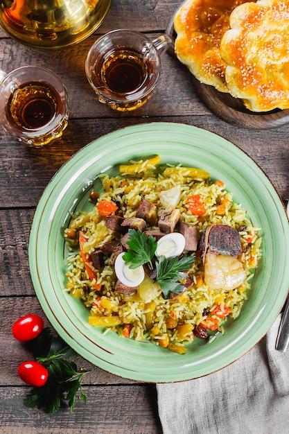 Национальный традиционный узбекский плов с мясом и рисом на деревянном столе. концепция восточной кухни. крупный план, вид сверху Premium Фотографии