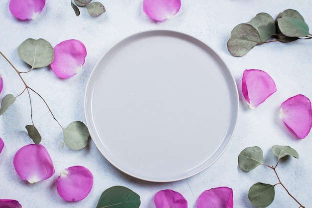 バラの花びらとユーカリの枝からフレーム Premium写真