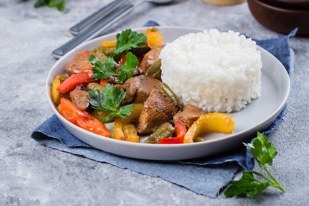灰色の石のテーブル背景に皿にご飯と野菜をチキンします。アジアンタイ料理 Premium写真