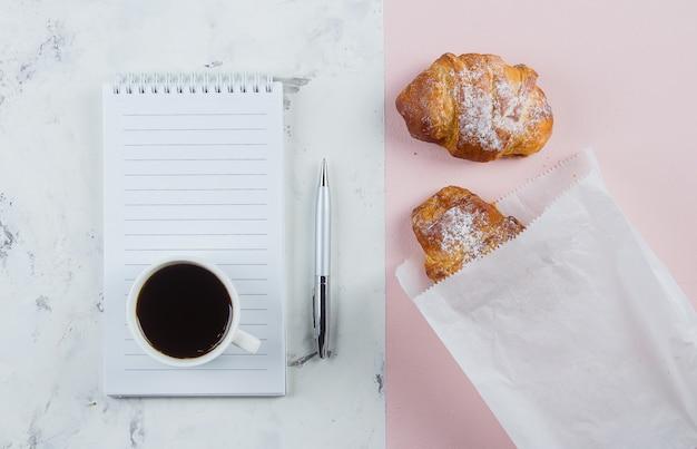 クロワッサンと空のノートブックと事業計画とデザインのアイデアのためのペンとコーヒー・マグ Premium写真