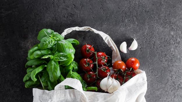食料品の再利用可能なバッグ。トートバッグ、最小限の無駄。バジル、チェリートマト、ニンニク、生地の袋 Premium写真