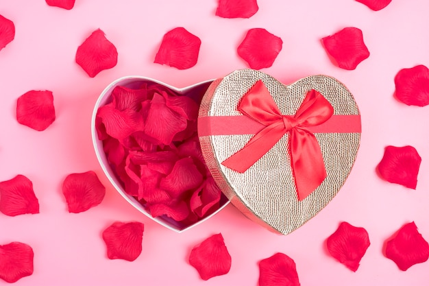 ピンクの背景の中にバラの花びらをハートの形のギフトボックスハッピーバレンタインデーのコンセプト Premium写真