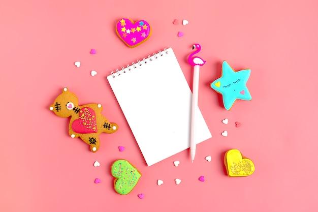 ロマンチックなテディベア、ジンジャーブレッドハート、スター、トレンディなピンクの背景のメモ帳 Premium写真