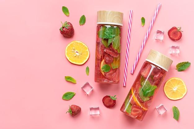 ストロベリー、水、夏のアイスドリンク、ストロベリー、レモン、ミントの葉とピンクの背景 Premium写真