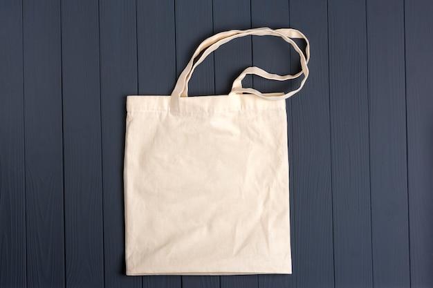 ダークグレーの木製テーブルにエコフレンドリーな不織布バッグ Premium写真