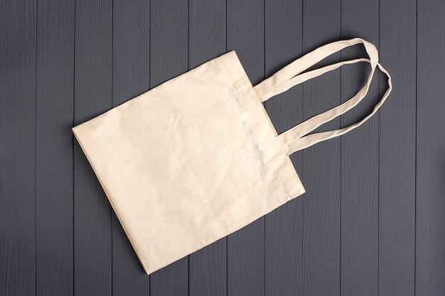 Экологичная нетканая сумка на темно-сером деревянном столе Premium Фотографии