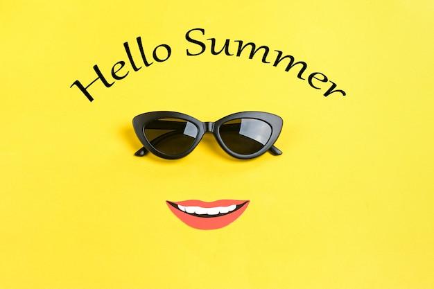 Надпись привет лето солнце в стильных черных очках, улыбающийся рот на желтом Premium Фотографии