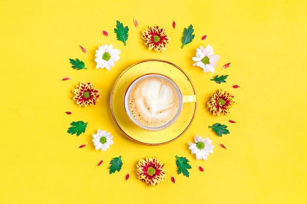 赤と白のアスターの花、緑の葉、黄色のホットコーヒーカプチーノのカップのパターン Premium写真