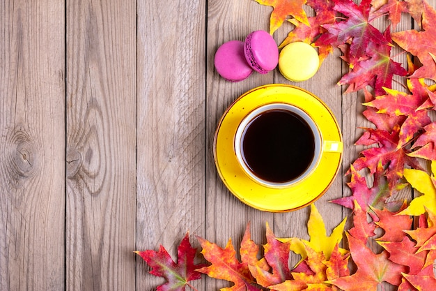 秋の落ちた黄色、オレンジ、赤の葉の木製テーブルの上のホットブラックコーヒーカップ Premium写真