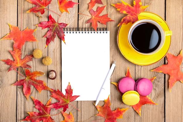 ブラックコーヒー、黄色のロリポップ、マカロン、メモ帳、秋の落ちたオレンジの葉と木製のテーブルとカップフラットレイアウト Premium写真