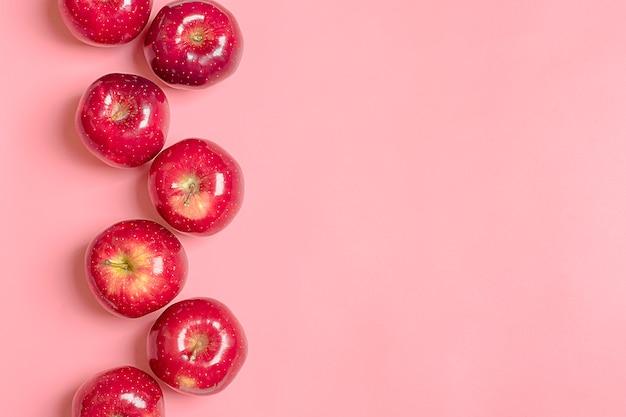 新鮮な収穫された赤いリンゴは、トレンドピンクの千年紀の背景にある。フルーツナチュラルオーガニック Premium写真
