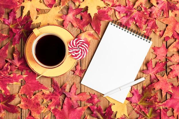 ブラックコーヒー、ロリポップ、マカロン、テキスタイルスカーフ、メモ帳、秋の落ちたオレンジの葉の木製テーブルとカップフラットレイアウト Premium写真