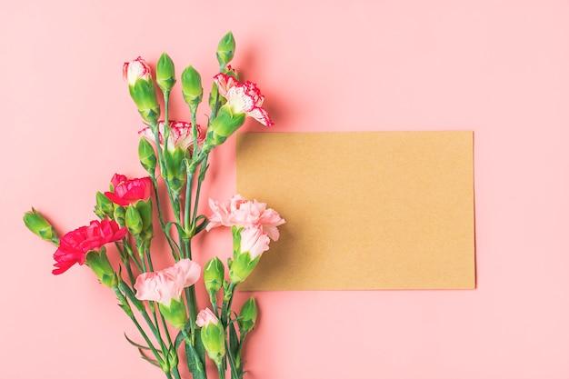 異なるピンクのカーネーションの花、ピンクの背景に白いノートのカラフルな花束 Premium写真