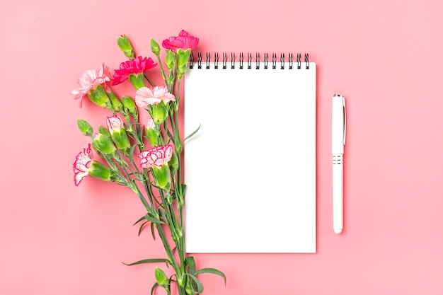 Красочный букет из различных розовых цветов гвоздики, белая тетрадь, ручка на розовом фоне Premium Фотографии