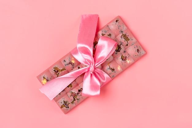 レーズンとピンク色の背景にデザートコンセプトに分離されたナッツとピンクのフルーツチョコレート Premium写真