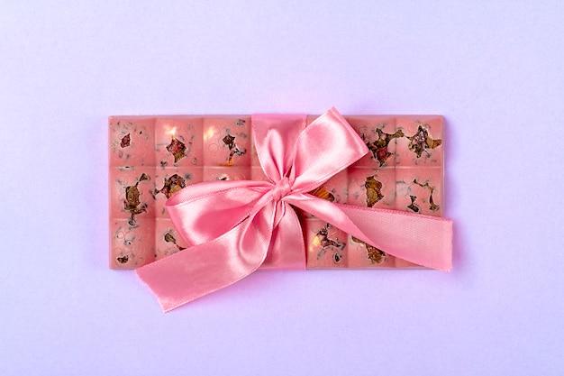 レーズンとナッツのライラック色の背景に分離されたピンクのフルーツチョコレートデザートタイムコンセプトキャンディショップ Premium写真