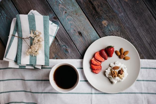 カッテージチーズ、イチゴとナッツ、一杯のコーヒーと木製のテーブルの上のタオル、健康食品、朝食プレート Premium写真
