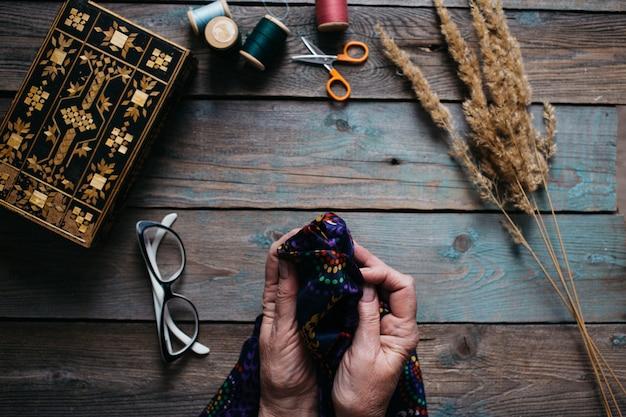 Женские руки шить на деревянный стол, ножницы, шкатулка, нитки, очки Premium Фотографии