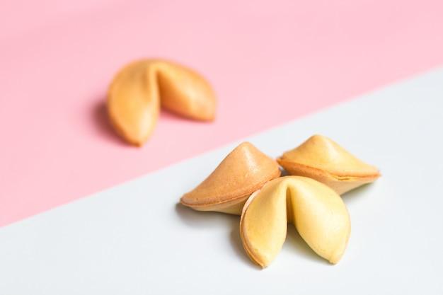 ピンクと青の背景にあるフォーチュンクッキー、パステルカラー Premium写真