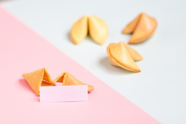 ピンクと青の背景にフォーチュンクッキー、パステルカラー、コピースペース Premium写真