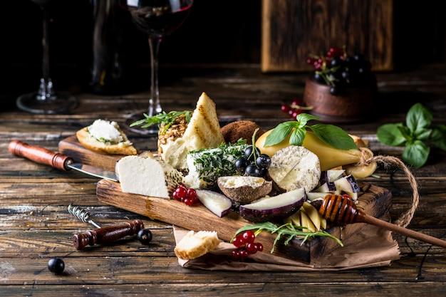 チーズ前菜の選択。赤スグリ、蜂蜜、バジル、ブドウ、素朴な木の板にナッツ Premium写真