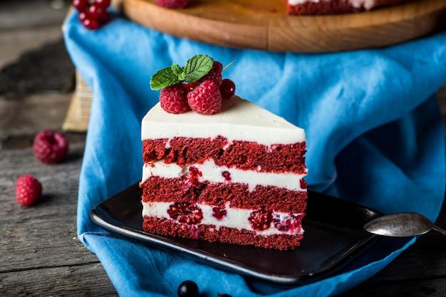 木板に赤いベルベットのケーキ。ケーキのスライス。ラズベリーケーキ。悪魔のケーキ。結婚式のデザート。誕生日ケーキ。 Premium写真