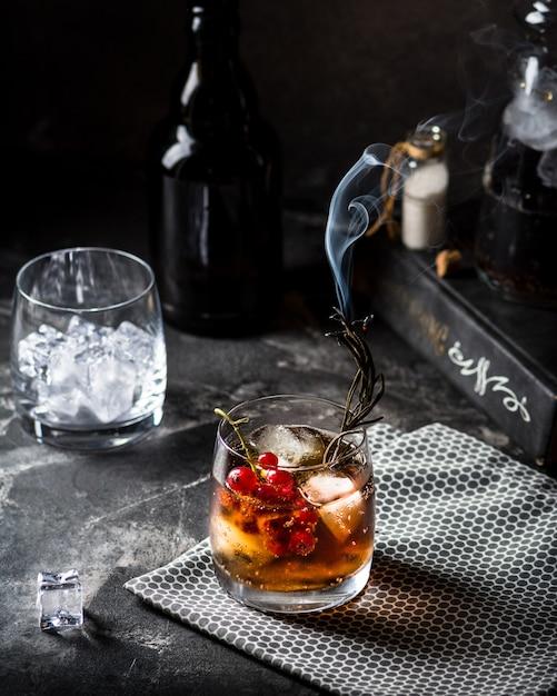 キューバリブレまたはロングアイランドアイスティーカクテル、濃い飲み物、コーラ、ライム、グラス入り氷、冷たいロングドリンクまたはレモネード。火とカクテル。煙とカクテル。 Premium写真