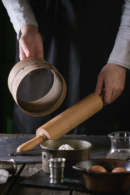 Женские руки с деревянной скалкой и ситом Premium Фотографии