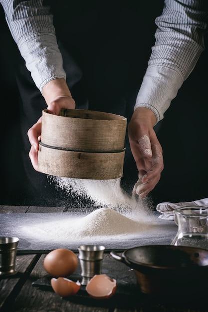 女性の手で小麦粉をふるいにかける Premium写真