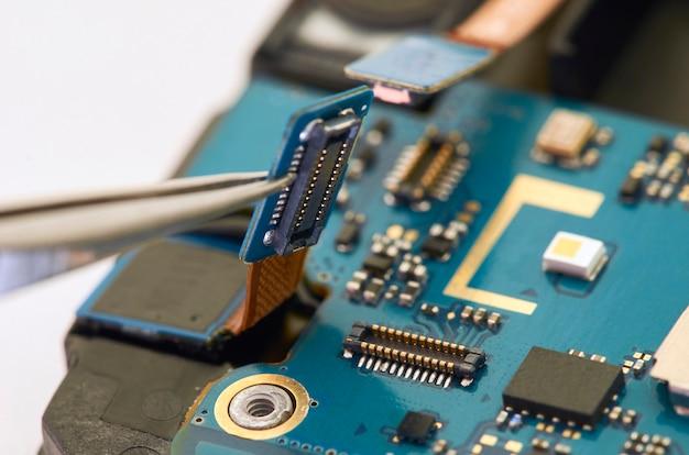 電気ボードを内側に見せるスマートフォンの分解。電話は固定しています Premium写真