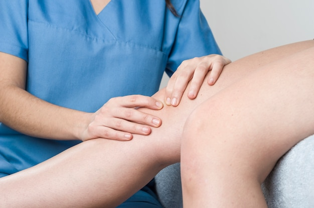 Физиотерапевт, мануальный терапевт делает мобилизацию надколенника, боль в колене Premium Фотографии